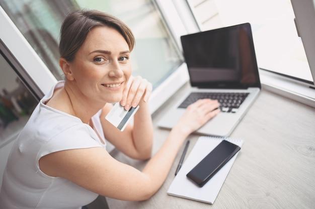 Mooie gelukkige vrouw met creditcard in de hand en met behulp van laptop computertoetsenbord. zakenvrouw of ondernemer werken. online winkelen, e-commerce, internetbankieren, zakgeldconcept Premium Foto