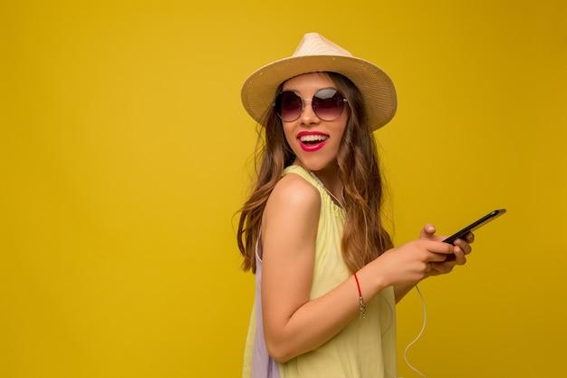 Mooie gelukkige vrouw met lang donker haar met hoed en zomerjurk poseren Gratis Foto