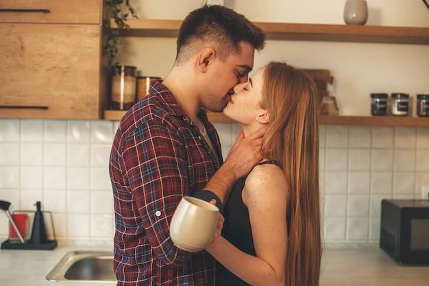 Mooie gember vrouw met sproeten kust haar minnaar terwijl ze een kopje thee drinkt in de keuken Premium Foto