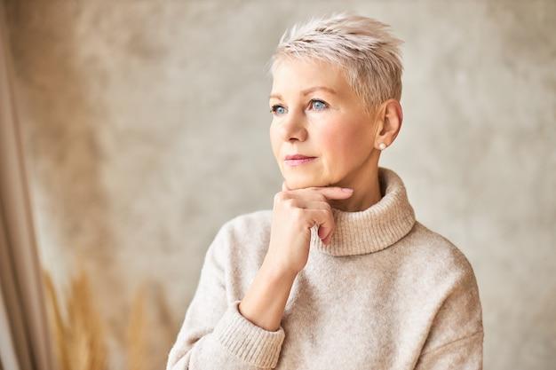 Mooie gepensioneerde vrouw, gekleed in gezellige trui en kort kapsel Gratis Foto
