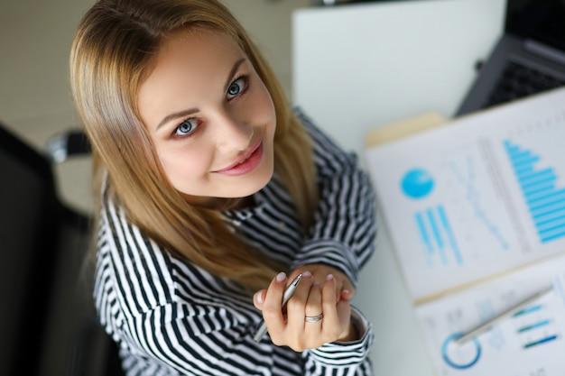 Mooie glimlachende bediendezitting bij werkende lijst Premium Foto