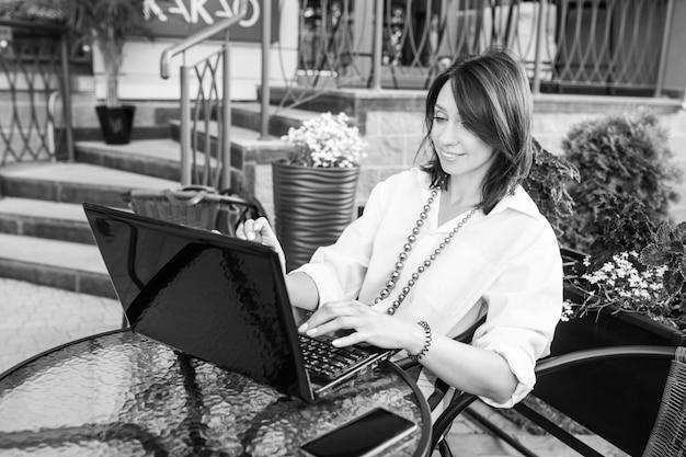 Mooie glimlachende bedrijfsvrouwenzitting in stadskoffie en het werken met haar laptop. zwart en wit beeld Premium Foto