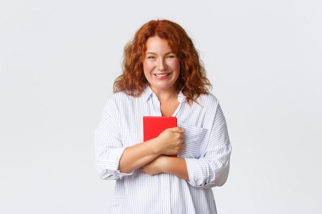 Mooie glimlachende roodharige vrouw van middelbare leeftijd die blij en tevreden kijkt, rode notitieboekplanner met vrolijke uitdrukking vasthoudt, plannen maakt, aantekeningen maakt, online cursus begint, witte muur. Premium Foto