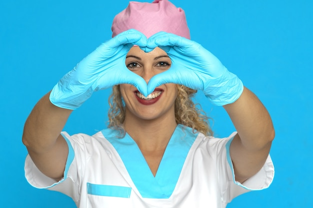 Mooie glimlachende verpleegster die een hart met handen toont Gratis Foto