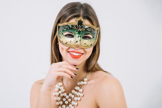 Mooie glimlachende vrouw die groen decoratief carnaval masker draagt Gratis Foto