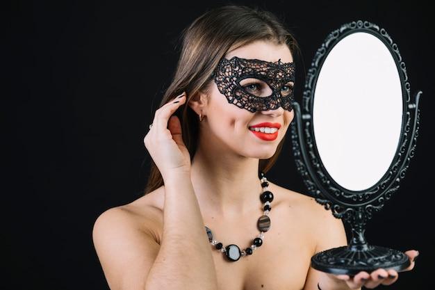 Mooie glimlachende vrouw die in carnaval masker in hand spiegel kijkt Gratis Foto