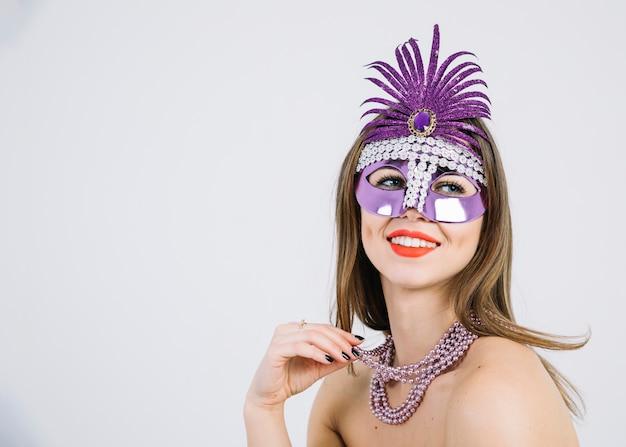 Mooie glimlachende vrouw die purper decoratief carnaval-masker op witte achtergrond draagt Gratis Foto