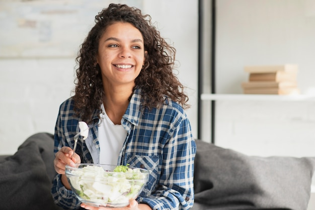 Mooie glimlachende vrouw die salade eet Gratis Foto