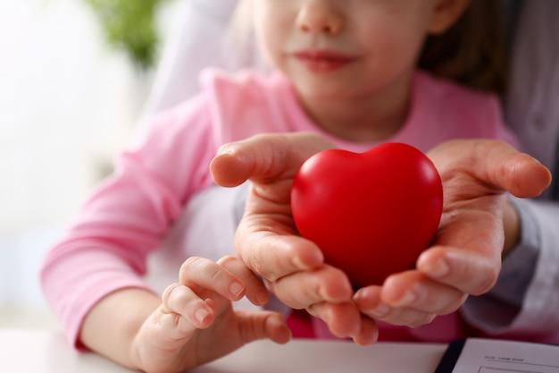 Mooie glimlachende vrouw en kind houden rode speelgoed Premium Foto