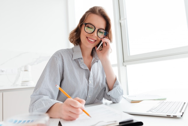 Mooie glimlachende vrouw in glazen die op mobiele telefoon spreken terwijl thuis het werken met documenten Gratis Foto
