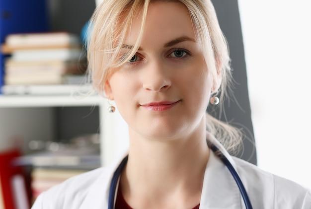 Mooie glimlachende vrouwelijke arts op werkplek portret Premium Foto