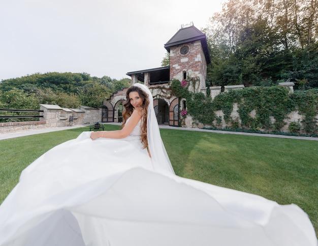 Mooie glimlachte bruid in luxe jurk op de achtertuin van het gras van het oude gebouw, Gratis Foto