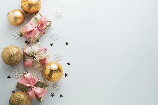 Mooie gouden geschenken gloden kerstballen op wit. kerstmis, feest, verjaardag. vier glimmende verrassingsdozen copyspace. creatieve plat lag bovenaanzicht. Premium Foto