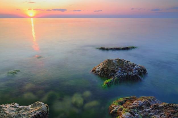 Mooie gouden zonsondergang over de rotsachtige kustlijn van de zwarte zee op de krim op zomerdag Premium Foto
