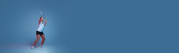 Mooie handicap vrouw oefenen in badminton geïsoleerd op blauwe achtergrond in neonlicht. levensstijl van inclusieve mensen, diversiteit en gelijkheid. sport, activiteit en beweging. copyspace voor advertentie. folder Gratis Foto