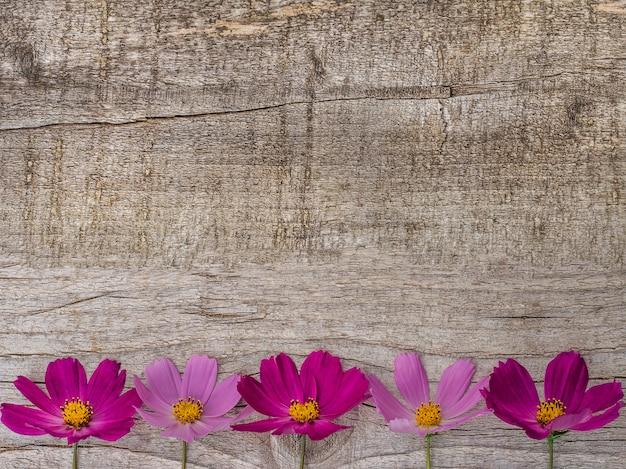 Mooie heldere bloemen die op houten oppervlakte liggen Premium Foto