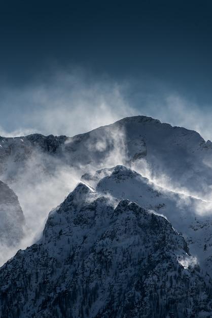 Mooie hoge besneeuwde en mistige bergen met sneeuw waait door de wind Gratis Foto