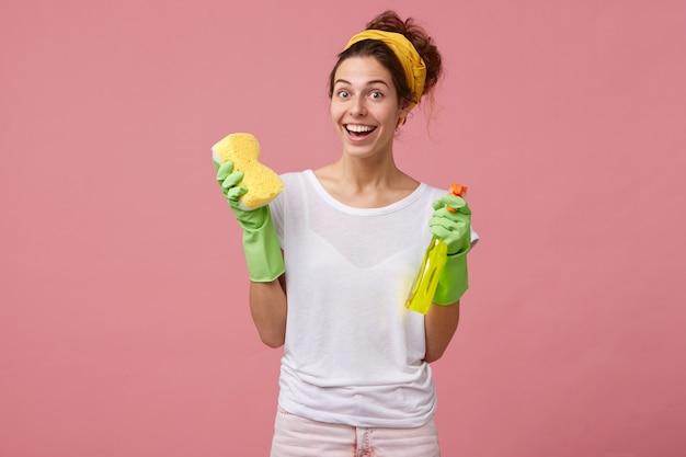 Mooie huisvrouw met gele hoofdband en wit t-shirt met dweil en wasspray op zoek gelukkig goed humeur te hebben en de voorjaarsschoonmaak in haar huis te willen doen Gratis Foto