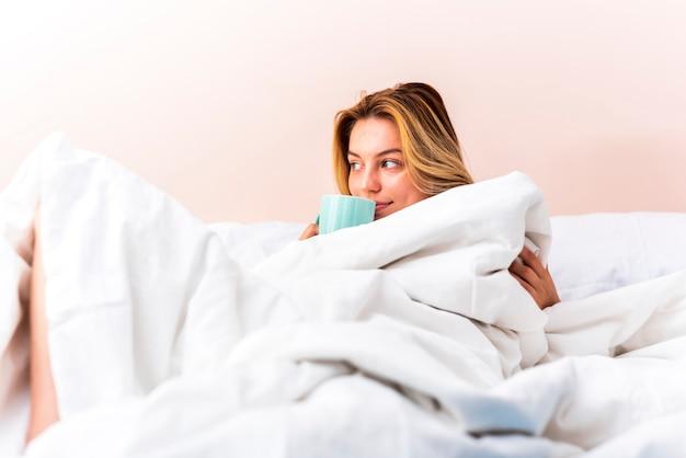 Mooie in bed legt en vrouw die weg kijkt Gratis Foto