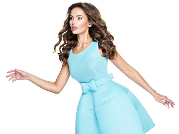 Mooie jonge aantrekkelijke vrouw met lang haar in blauwe jurk. aantrekkelijke mannequin poseren op witte achtergrond. Gratis Foto