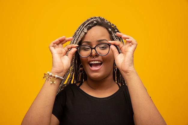 Mooie jonge afrikaanse amerikaanse vrouw met gevreesde haar en oogglazen op geel Premium Foto
