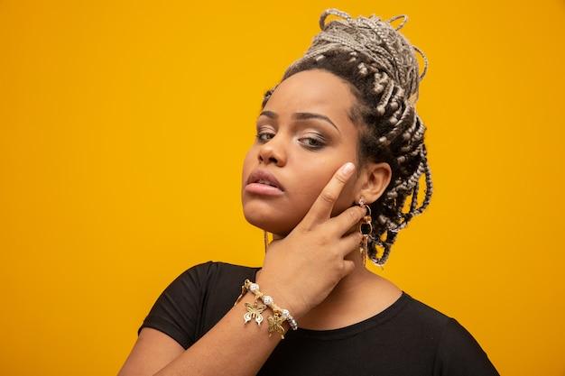 Mooie jonge afrikaanse amerikaanse vrouw met ontzettingshaar op geel Premium Foto
