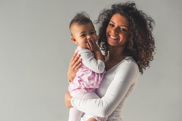 Mooie jonge afro-amerikaanse vrouw en haar schattige baby Premium Foto
