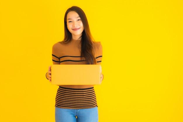 Mooie jonge aziatische het kartondoos van de vrouwenholding in haar hand op gele muur Gratis Foto