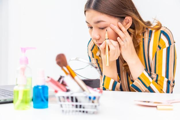 Mooie jonge aziatische vrouw die haar make-up op Premium Foto