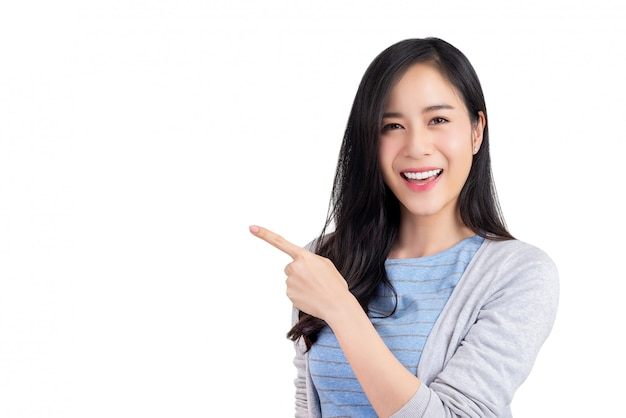 Mooie jonge aziatische vrouw die hand aan lege ruimte opzij richten Premium Foto