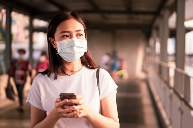 Mooie jonge aziatische vrouw die het beschermende masker draagt tijdens het reizen in de stad Premium Foto