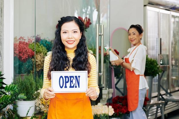 Mooie jonge aziatische vrouw stond met open zucht in bloemenwinkel, haar collega bloemen sproeien met zoet water Premium Foto