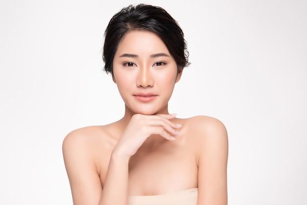 Mooie jonge aziatische vrouw wat betreft zachte wang en glimlach met schone en frisse huid. geluk en vrolijk met ,, beauty and cosmetics concept, Premium Foto