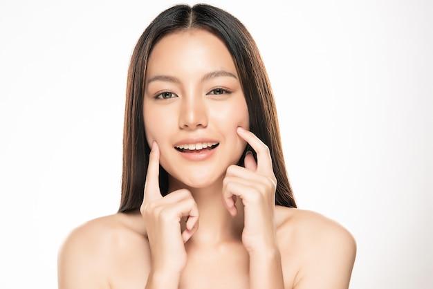 Mooie jonge aziatische vrouw wat betreft zachte wang en glimlach met schone en frisse huid. geluk en vrolijk met, geïsoleerd op witte muur Premium Foto