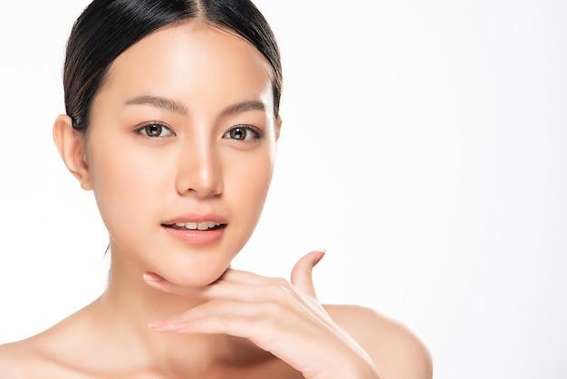 Mooie jonge aziatische vrouw wat betreft zachte wang en glimlach met schone en frisse huid. geluk en vrolijk met, geïsoleerde, schoonheid en cosmetica concept, Premium Foto
