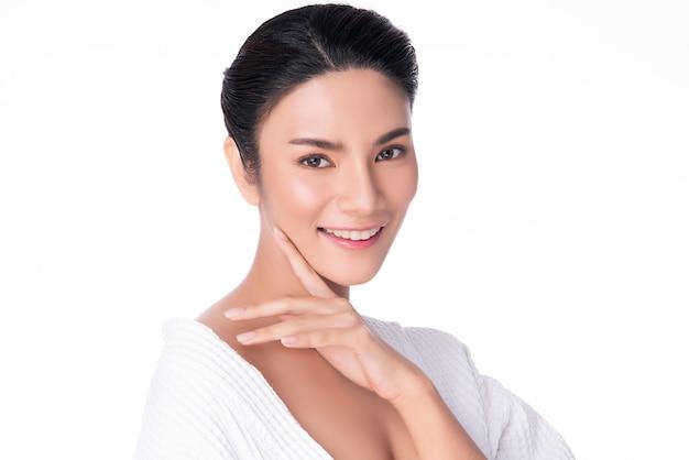 Mooie jonge aziatische vrouw wat betreft zachte wangglimlach met schone en verse huid geluk en vrolijk, geïsoleerd op wit, schoonheid en schoonheidsmiddelen Premium Foto