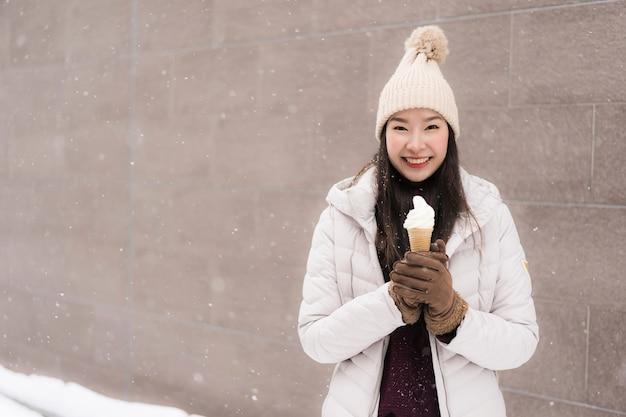 Mooie jonge aziatische vrouwenglimlach en gelukkig met roomijs in sneeuw wintertijd Gratis Foto