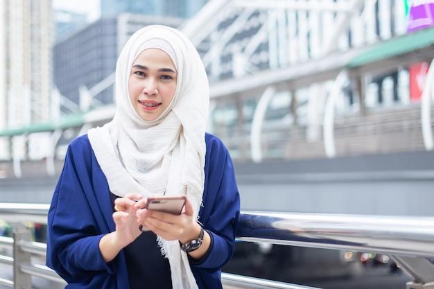 Mooie jonge aziatische zakelijke moslimvrouw in een pak die hoofddoek (hijab) uesing smartphone dragen Premium Foto