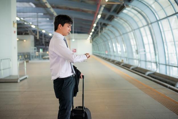 Mooie jonge aziatische zakenmanreiziger die klok in hand met bagage kijken, die op trein bij station, reis en vakantie wachten. Premium Foto