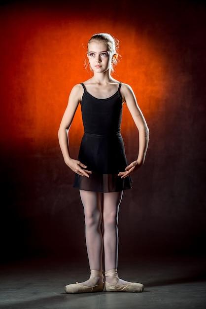 Mooie jonge ballerina danst in de studio op een donkere muureen kleine danser. balletdanser. Premium Foto