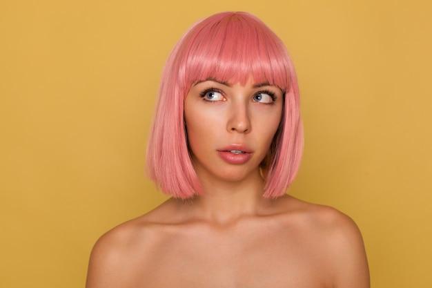 Mooie jonge blauwogige roze haired vrouw met korte trendy kapsel op zoek bedachtzaam naar boven terwijl staande over mosterd muur Gratis Foto