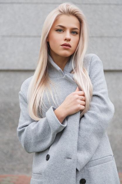 Mooie jonge blonde haren vrouw in grijze jas Premium Foto