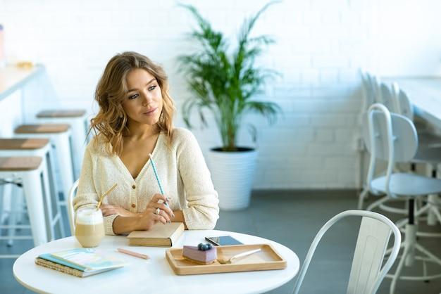 Mooie jonge blonde student met potlood over boek aan tafel in café zitten, huiswerk denken en koffie drinken Premium Foto