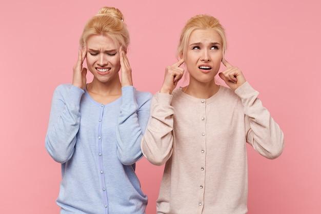 Mooie jonge blonde tweeling hoorde een onaangenaam geluid waarvan er een ring in de oren is en een hoofd splitst, geïsoleerd op een roze achtergrond. Gratis Foto