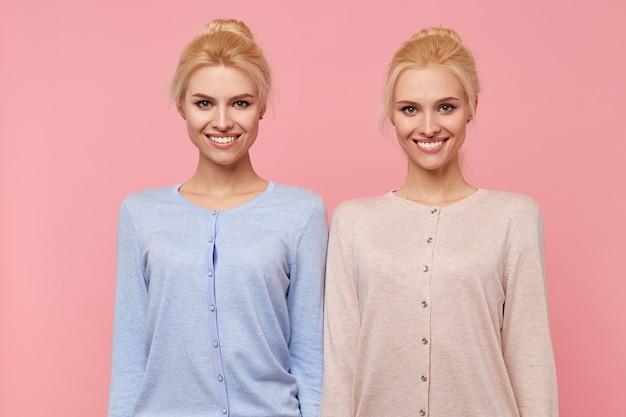 Mooie jonge blonde tweeling in een goed humeur, in grote lijnen lachend in de camera geïsoleerd op roze achtergrond. Gratis Foto