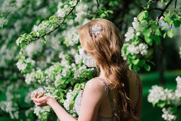 Mooie jonge bruid in een trouwjurk en een wit medisch masker op haar gezicht in de buurt van een bloeiende magnolia. covid-19 beschermt. Premium Foto