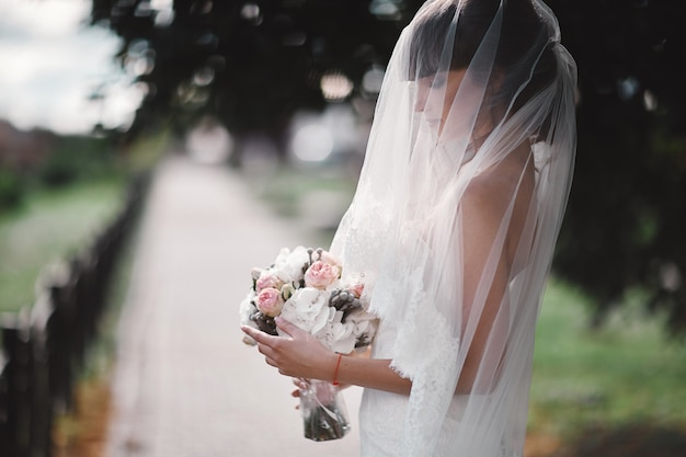 Mooie jonge bruid in een witte luxekleding en in een bruidssluier met een boeket van bloemen openlucht stellen. bruiloft portret. kopie ruimte Premium Foto