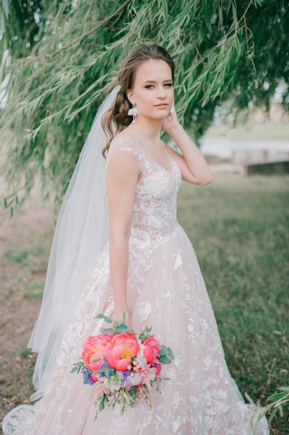 Mooie jonge bruid in het witte huwelijkskleding stellen openlucht met boeket van bloemen. Premium Foto