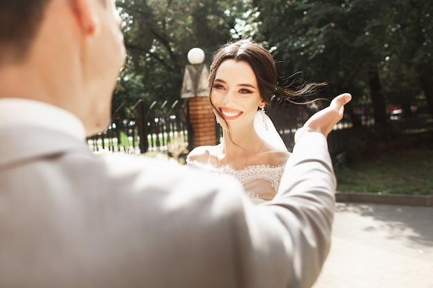 Mooie jonge bruid in stijlvolle witte jurk, glimlachend ontmoet haar bruidegom in het park Premium Foto