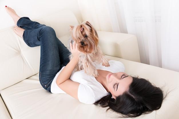 Mooie jonge brunette meisje speelt met haar yorkshire terriër thuis vaststelling op de bank en houdt haar huisdier Premium Foto